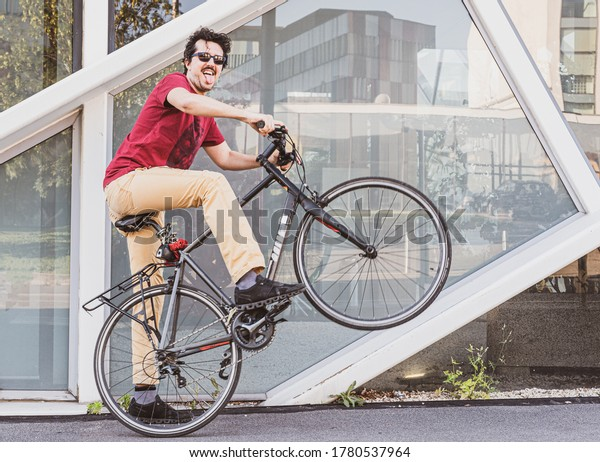 exuberant young man rides his bike, enjoys playing with his bike, facial grimace with tongue out, urban mobility concept and street lifestyle