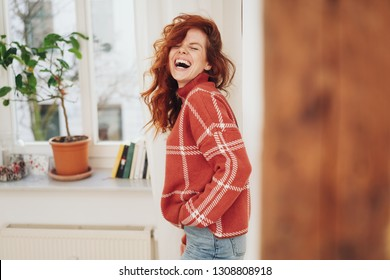 Exuberant young woman laughing out loud as she stands with her hands in her jeans pockets turning to laugh at camera