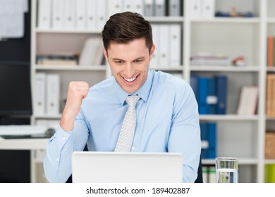 Exultant businessman making a fist and cheering at information on his laptop computer screen as he celebrates a success or achievement