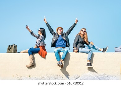 Exultant friends with man hands up and happy woman freezing the moment taking selfie - Students joy and victory gesture sitting together under blue sky background - Concept of people good emotions