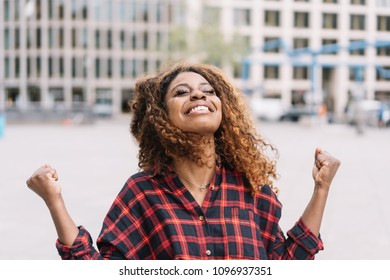 Exultant young African woman rejoicing clenching her hands and looking up with a beaming pleased smile in an urban street