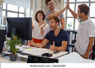 Exultant young business team cheering at good news on their desktop computer as they congratulate each other on a victory or success