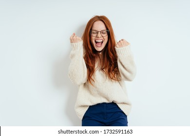 Exultant young redhead woman cheering and clenching her fists in excitement after receiving good news standing against a white wall with copy space