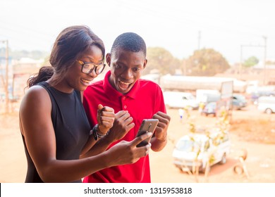 exxited young African man and woman happy and jubilant about something they're looking at on a mobile phone