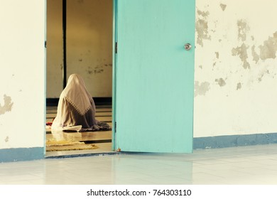 EYDHAFUSHI, MALDIVES - 13/01/2013: Lone Muslim Maldivian woman wearing hijab prays at the local women's mosque