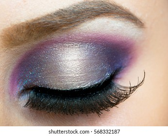 Eye with beautiful makeup with pink and purple shadows and long false eyelashes. Closed girl's eye with an evening female make-up