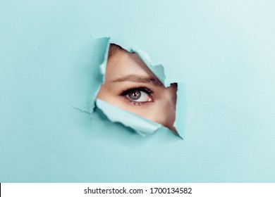 Eye of the beautiful woman looking through hole in blue paper. Spy eye watching through hole. Copy space.