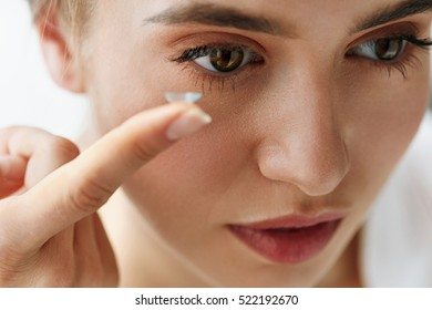 Eye Care And Contact Lenses For Eyes. Closeup Of Beautiful Woman Face With Smooth Skin And Perfect Makeup Applying Eyelens With Finger. Female Model Putting In Contact Eye Lens. Vision And Health