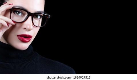 Augenpflege und Augenheilkunde Herrliches Modellmädchen mit heller Make-up, rote Lippen und Nägel mit trendiger Brille. Schönes Modeportrait einzeln auf schwarzem Hintergrund mit Kopienraum.