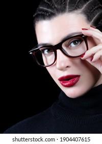 Augenpflege und Augenheilkunde Stilvolle Frau in trendiger Brille, Hals-Pullover und perfekt Make-up. Schöne, liebevolle Frau mit angesagter Frisur und roten, saftigen Lippen, die ihre elegante Brille berührt