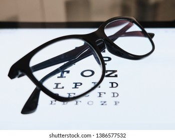 eye chart on tablet and the glass with E Standard Logarithm Eyesight Table on top of the light screen