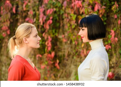 Eye contact. Women looking at each other with attention. Rivalry and leadership. Blonde brunette competitors. Female rivalry. Friendship problems rivalry and jealousy. Pretty girls friends sisters.