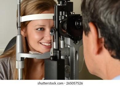 Eye Doctor druring a test with young patient in his office