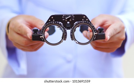 The eye doctor is preparing the eyeglass frame to gaze on the customer as an ophthalmologist's device.