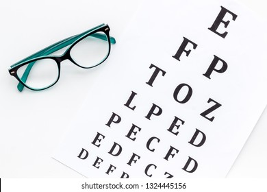 Eye examination. Eyesight test chart and glasses on white background top view