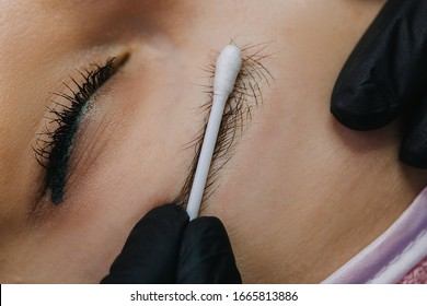 Eye and eyebrow close up. A hand in a black glove holds a cotton swab and pushes the eyebrow hairs to see the first drawn hairs with microblading.