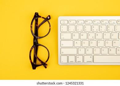 Eye glass and Keyboard on yellow Cardboard