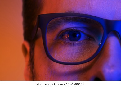 Eye and glasses - caucasian man's face close up (macro) in colorful light. Blue and orange tonal transitions.