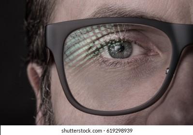 Eye and glasses - caucasian man's face close up (macro). Black background, dark moody light.