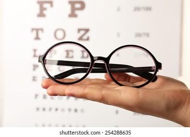 Eye glasses in female hand on eyesight test chart background