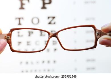 Eye glasses in female hands on eyesight test chart background