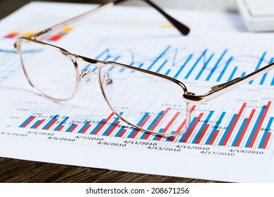 Eye glasses lying on papers with graphs and diagrams