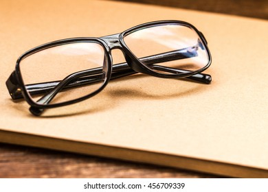 Eye glasses on beige grained old paper for painting in sepia on dark wooden table background