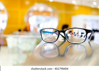 Eye glasses on table in library, can see people reading books through the lens
