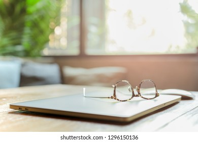 Eye glasses on top of laptop at business workplace in blur background.
