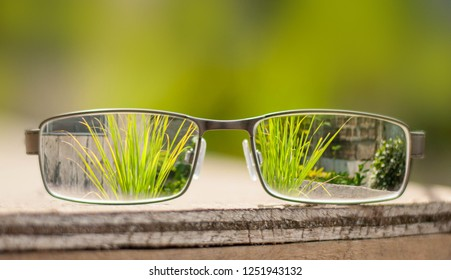 Eye glasses placed on top of a wooden table to see through the background