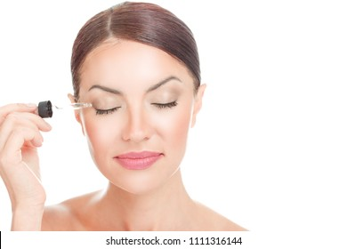 Eye Lash gel Serum. Woman applying serum essence essential oils to her eyelashes for growth strong effect solution with eyes closed isolated on white. Positive face expression mixed race latina girl