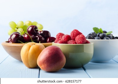 Eye level shot of various fresh fruits, in separate bowls and on light blue painted wood plank table with copy space above.