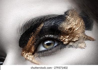 Eye with long eyelashes and black and gold makeup closeup
