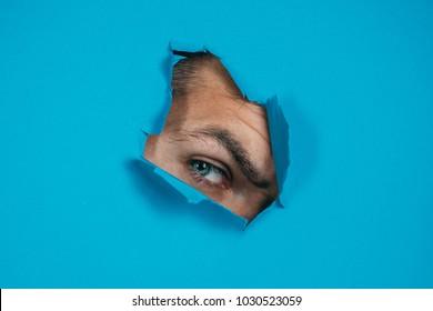 Eye looking through hole in paper. Spy eye watching through a hole. Eye looking through hole in blue paper.