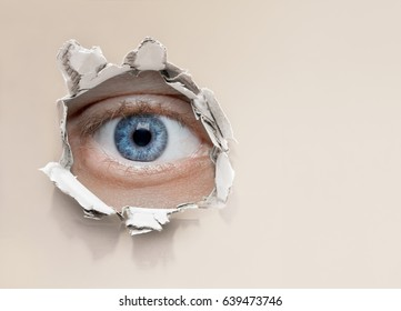 eye looking through hole in wall