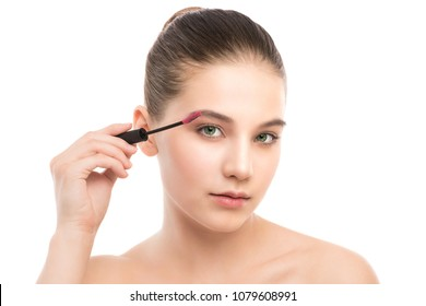 Eye make up apply. Mascara applying closeup, long lashes. Mascara brush. Portrait of beautiful young brunette woman with perfect fresh clean face skin. Eyelashes extensions. Make-up for green eyes