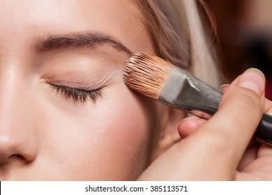Eye makeup woman applying eyeshadow powder with make up brush