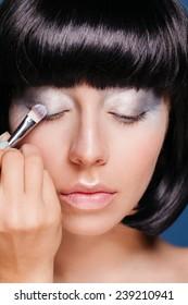 Eye makeup woman applying silver eyeshadow powder