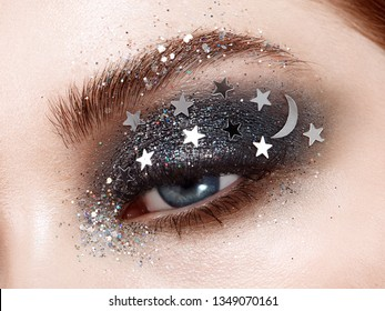 Eye makeup woman with decorative stars. Perfect makeup. Beauty fashion. False Eyelashes. Cosmetic Eyeshadow. Make-up detail. Eyeliner. Creative make-up the night sky with stars