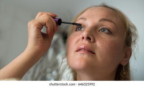 Eye makeup.Young woman applying mascara make-up