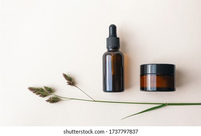 Eye moisturizer cream and serum in brown glass bottle and jar and meadow herb on light beige background. Concept eco organic natural cosmetic products for skincare
