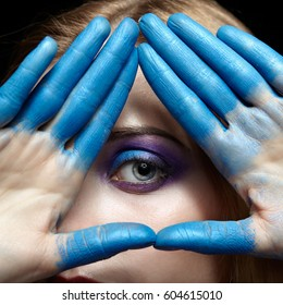 Eye of Providence, eye pyramid Illuminati and mason symbol made of hands and female face with blue paint on fingers