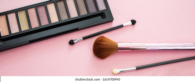 Eye shadows pallete set neutral colors and brushes against pink background, closeup view. Professional tools for make up, beauty salon, cosmetics concept