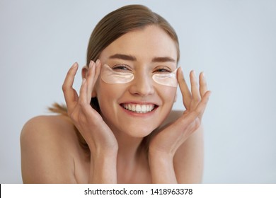 Eye skin beauty. Happy woman with transparent under eye patch, beauty mask on face portrait. Smiling girl using translucent collagen pad on white background