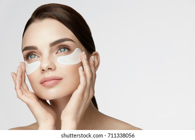 Eye Skin Treatment. Portrait Of Beautiful Young Woman With Natural Makeup Applying White Under Eye Patches, Beauty Mask On Face. High Resolution