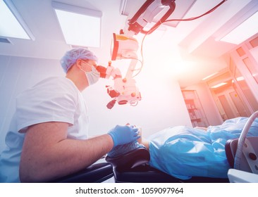 Eye surgery. A patient and surgeon in the operating room during ophthalmic surgery. Patient under surgical microscope. Vision correction