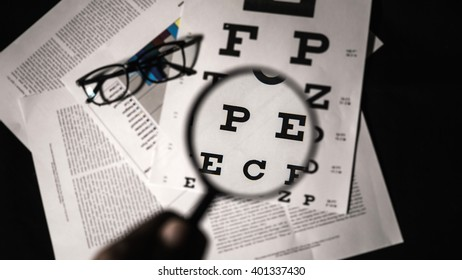 Eye test examination with a magnifier.