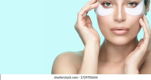 Augentherapie-Pflaster. Gesunde Haut mit perfekter, sauberer Haut unter Augenpflastern. Anti-Alterungs-Feuchtigkeitsspendende Augenmaske. Kosmetologie, Spa und Hautpflege Schönheit. Blauer Hintergrund mit Kopierraum