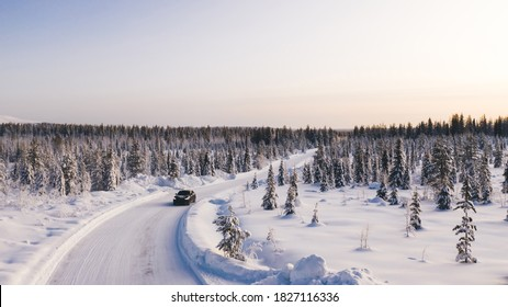 Bird's eye view of vehicle car moving on rural road having good insurance for winter weather, aerial view of suv automobile driving in scenery area surrounded by coniferous forest