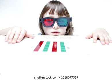 Eye vision therapy. Child with red green reading bar and glasses